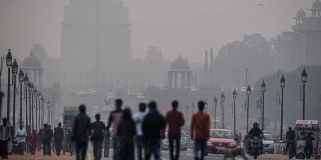 Indian pedestrians walk near smog enveloped government offices on Rajpath in New Delhi on December 1, 2015. India's capital, with 18 million residents, has the world's most polluted air with six times the amount of small particulate matter (pm2.5) than what is considered safe, according to the World Health Organization (WHO). The air's hazardous amount of pm2.5 can reach deep into the lungs and enter the blood, causing serious long term health effect, with the WHO warning India has the world's highest death rate from chronic respiratory diseases. India, home to 13 of the world's top 20 polluted cities, is also the third largest emitter of greenhouse gases behind the United States and China. Rich countries should not force the developing world to abandon fossil fuels completely, Indian Prime Minister Narendra Modi said at the UN climate summit in Paris on December 1. Almost a third of India's population remains in severe poverty with limited access to electricity, and its government sees little chance of boosting their prospects without turning to cheap and plentiful coal. AFP PHOTO / ROBERTO SCHMIDT / AFP / ROBERTO SCHMIDT (Photo credit should read ROBERTO SCHMIDT/AFP/Getty Images)